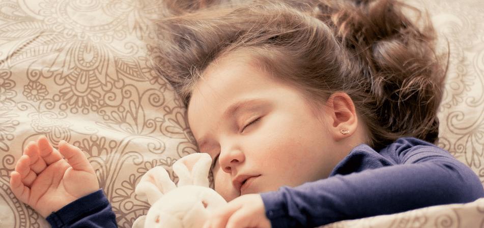 Bambina che dorme con pupazzo